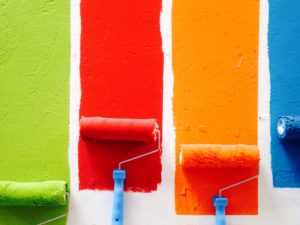 paint rollers with red, blue, green, and orange paint stripes