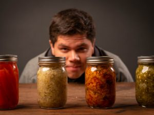 man squatting in front of jars full of preserved vegetable